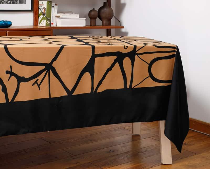 """Nappe """"Alvéole"""" en polyester recyclé, sur une table dans un salon."""