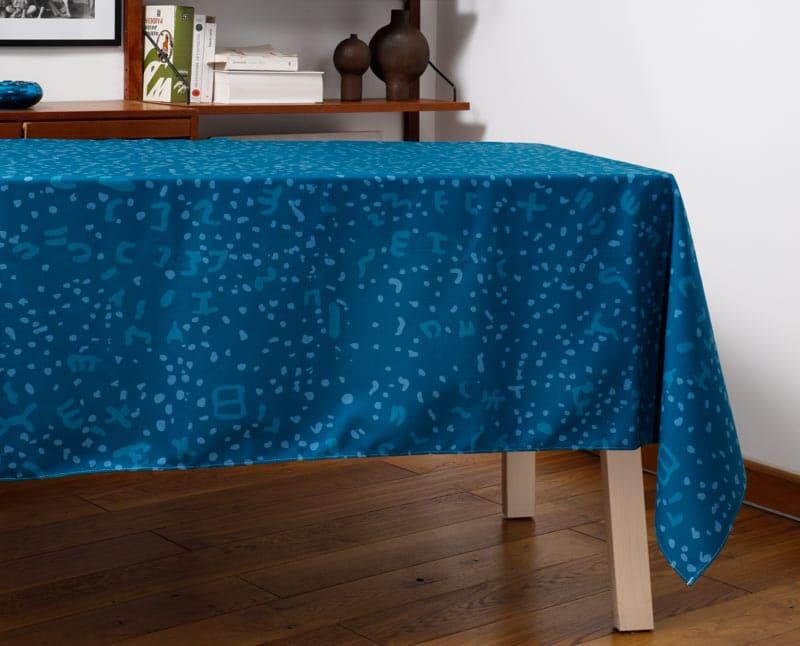 """Nappe """"Constelle"""" en polyester recyclé natté, dressée sur une table dans un salon."""