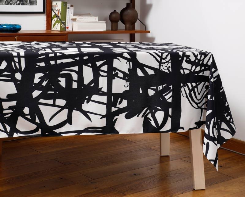"""Nappe """"Griffes"""" en polyester recyclé natté, dressée sur une table dans un salon."""