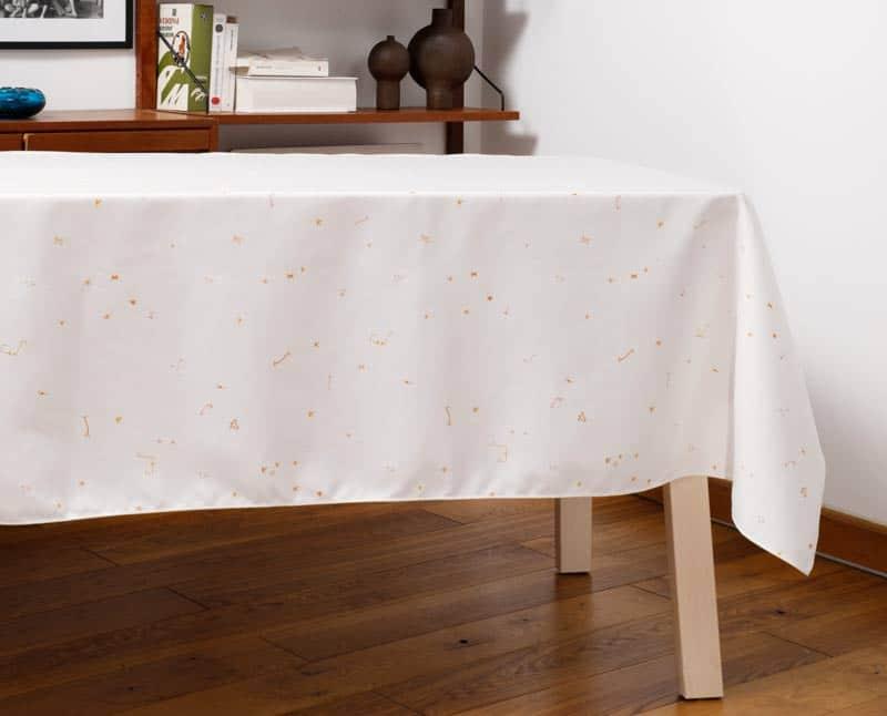 """Nappe """"Ouistiti"""" en polyester recyclé natté, dressée sur une table dans un salon."""