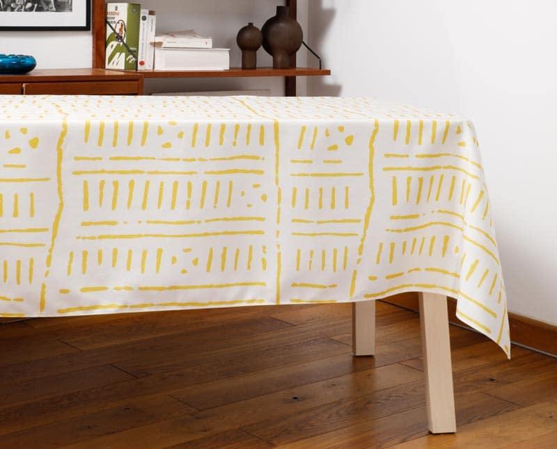 """Nappe """"Zeste"""" en polyester recyclé natté, dressée sur une table dans un salon."""